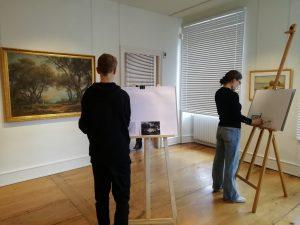 Personnes peignant devant un tableau